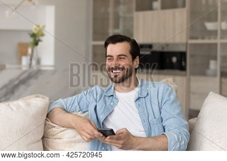 Overjoyed Laughing Young Man Distracted From Smartphone Sitting On Couch