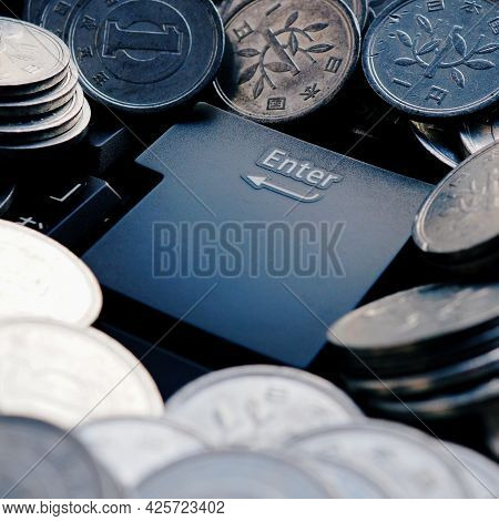 Japanese Money Lies Around The Enter Button. 1 Yen Coins Are On The Keyboard Of A Computer Or Laptop