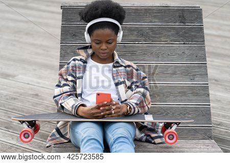 Serious African Woman Skater Relax After Skateboarding Texting In Smartphone With Longboard On Knees