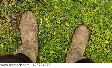 The Legs Are Shod In Old Boots. Farmer's Feet In Boots Standing On Green Grass.