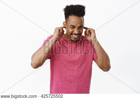 Turn Off This Loud Music. Displeased And Bothered African American Guy Squinting, Clench Teeth And S