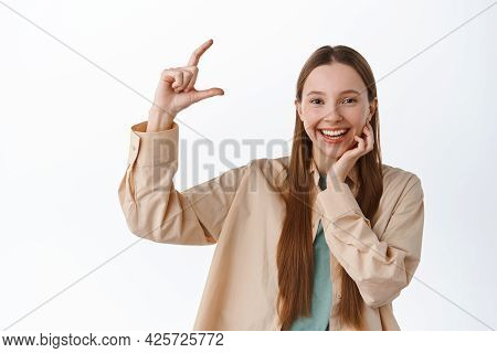 Cheerful Gen-z Girl Showing Small Size Tiny Thing, Smiling Pleased, Demonstrate Something On Copy Sp