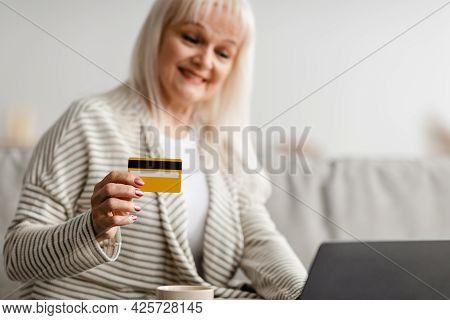 Smiling Mature Woman Using Credit Card At Home