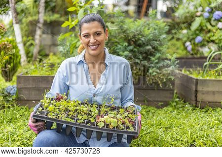 Woman Sitting In Her Garden With Germination Tray