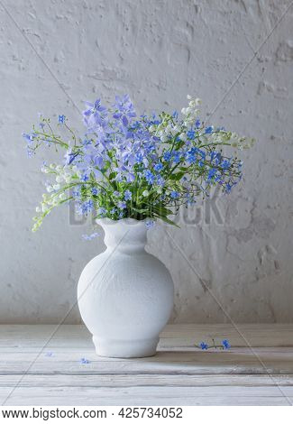 Spring Flowers In Vase On Background White Old Wall