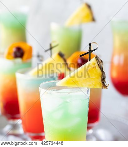 Close Up Of Several Colourful Icy Cocktails Garnished With Pineapple Wedges.