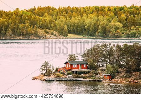 Sweden. Many Beautiful Red Swedish Wooden Log Cabin House On Rocky Island Coast In Summer. Lake Or R