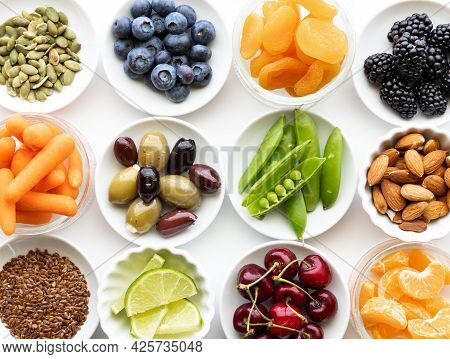 Top Down View Of Several Small Dishes Filled With Various Types Of Fresh Whole Raw Foods.