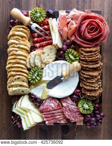 Top Down View Of A Meat And Cheese Charcuterie Board Against A Wooden Background.