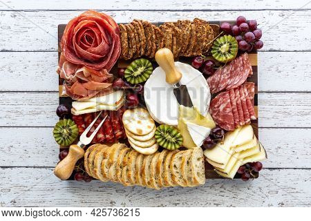 Top Down View Of A Meat And Cheese Charcuterie Board On A Light Wooden Table.