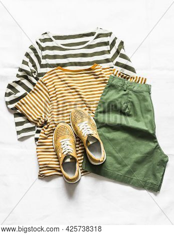 Women's Cotton Bermuda Shorts, Two T-shirt, Yellow Leather Sneakers On A Light Background, Top View.