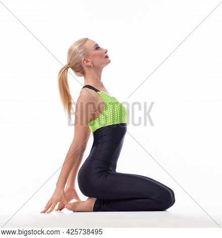 Preparing For Training. Studio Shot Of An Attractive Fitness Woman Sitting On Her Knees Stretching H