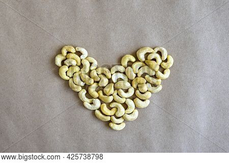 Heart Made Of Cashew Nuts, On Gray Craft Paper. Close-up. Selective Focus.