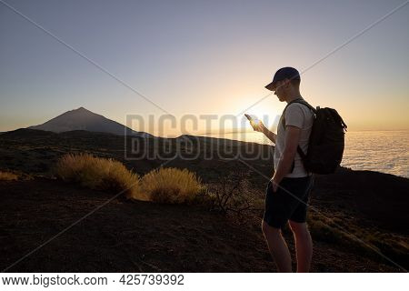 Hiker Using Mobile Phone On Hill Above Clouds At Sunset. Young Man With Backpack Against Landscape.