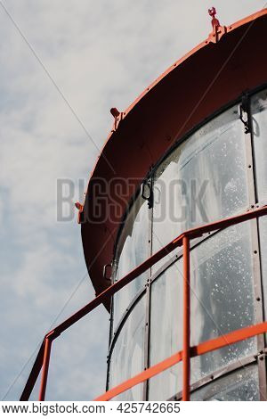 Close-up Of Lighthouse Windows Against Blue Sky. Lighthouse With Red Metal Protective Barriers And R