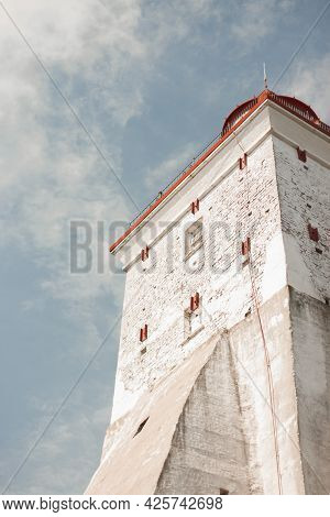 White Brick Building Against A Blue Sky With Red Protective Barriers And A Roof. Hiiumaa, Estonia