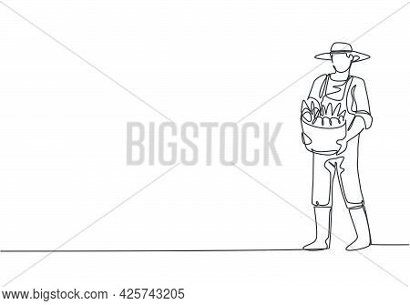 Continuous One Line Drawing Young Male Farmer Carrying A Basket Full Of Fruit With His Hands In Fron