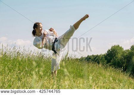 Teen Girl Practicing Karate Kata Outdoors, Performs The Mawashi Geri Kick