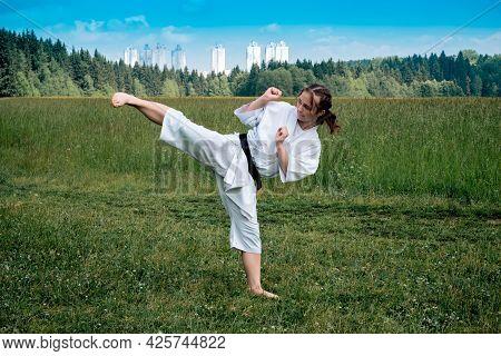 Teen Girl Practicing Karate Kata Outdoors, Performs The Yoko Geri Kick