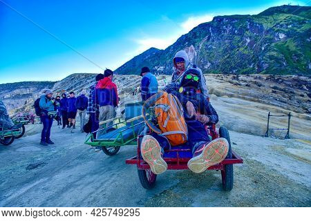 Tourists Use A Service Cart To Visited To See View Of Ijen Crater Lake And Blue Flame Early Morning.