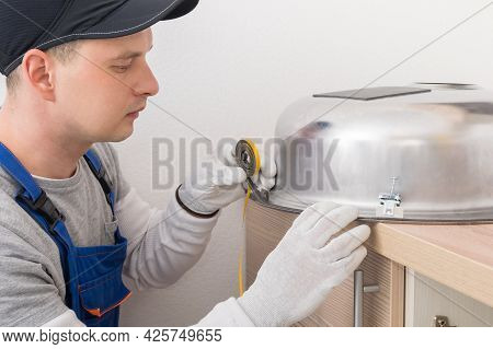 A Kitchen Furniture Worker Glues A Special Tape To The Sink To Keep It Tight