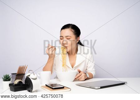 Asian Woman Eating Instant Noodles After Work Overtime At Office.