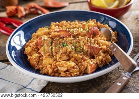 A Bowl Of Delicious Lobster Saffron Risotto On A Rustic Wood Table Top.