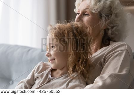 Adorable Preteen Girl Relax On Couch In Loving Granny Arms