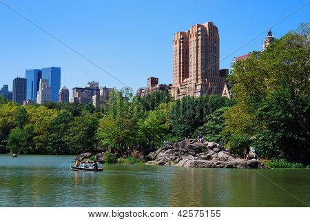 New York City Central Park with Manhattan skyline skyscrapers and blue sky with boat in lake. poster