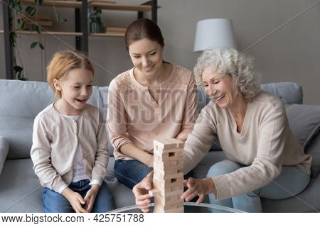 Little Girl Build Tumbling Tower With Mom And Old Grandma