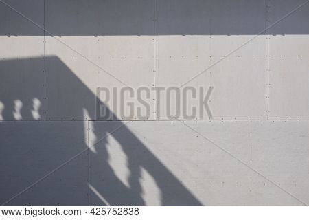 Sunlight And Balcony Shadow On Surface Of Gray Gypsum Wall Background