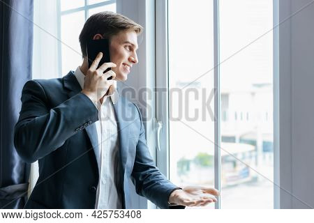 Businessman Making Phone Call Standing Near Window In Office At Workplace Happy Handsome Business Ma
