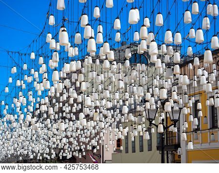 A Lot Of White Lamps Hang Over The Street. Illumination And Decoration Of The Street.