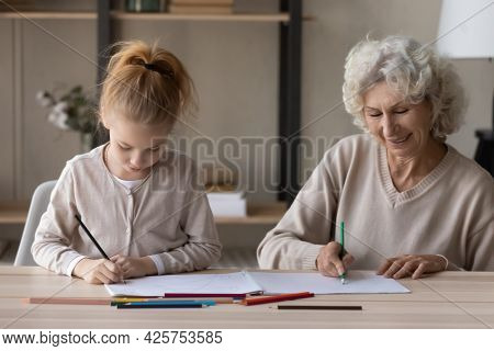 Caring Senior Grandmother Assist Preteen Grandchild To Paint Coloring Book