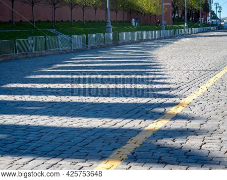 Long Shadows From The Teeth Of The Wall On The Stone Paving Stones. Outlines On The Road. Urban Land