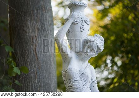 Sculpture Of A Girl In The Spring Park. An Old Statue In A Park Of A Sensual Semi-nude Greek Or Ital