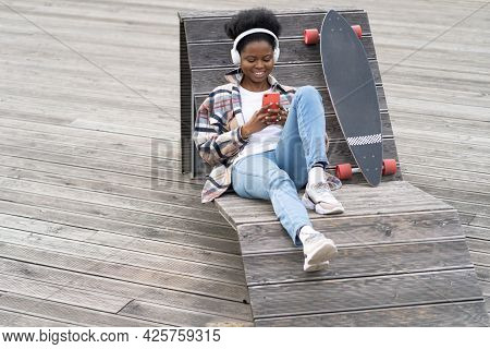 Young African Woman Skater Use Smartphone Texting Sit On Bench In Modern Urban Space With Longboard