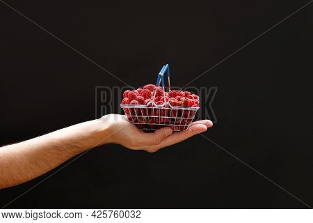 A Mans Hand Holds A Mini Grocery Shopping Basket With Fresh Raspberries On A Dark Background