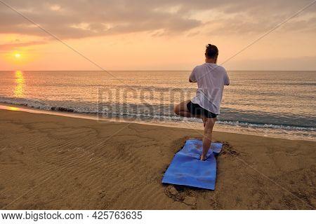 Man Practices Vrikshasana At Sandy Beach In Early Morning. Man Stands Balancing In Tree Pose Asana A