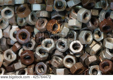 Many Old Used Screw-nuts Background, Dark Shining Nuts Size 16mm