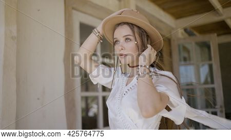Beautiful Young Woman Posing In Dress On Veranda. Action. Summer Image Of Young Woman In Dress And C