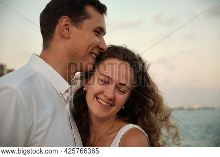 Romantic Date On A Sea Coast. Young Adult Woman And Man Embracing Each Other And Smiling Against Sea
