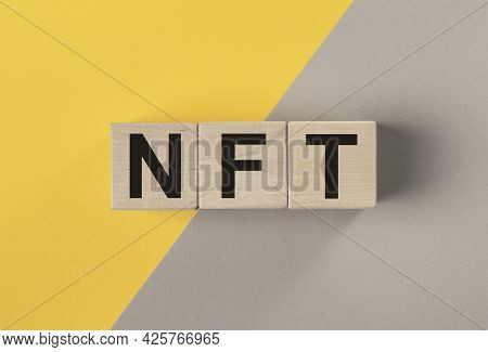Nft Acronym On Wooden Dices On Yellow And Gray Background.