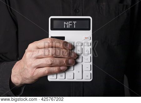 Nft Acronym On White Calculator In Hand Over Black Background.