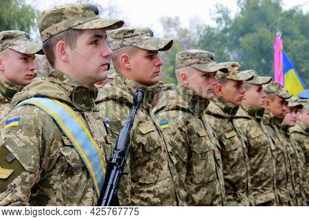 Military Parade In Ukraine. A Line Of Soldiers Of Ukrainian Army With Weapons And Flags Is Parade On