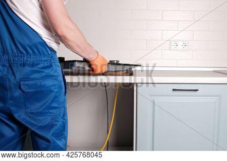 Serviceman Installs  New Gas Hob In  Kitchen Countertop, Close-up