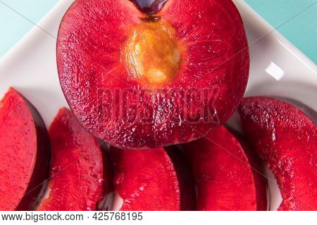 On A White Saucer, A Large Plum, Cut In Half, With Slices Next To It.