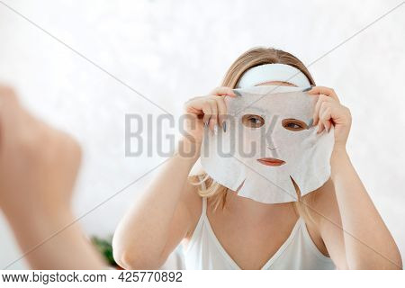 Woman Apply Mask Sheet On Face. Facial Skincare Cloth Mask. Teenage Girl Do Beauty Face Care Therapy