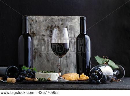 Glass Of Red Wine With Snacks And Cheese On Dark Background. Glass And Bottles Of Red Vintage Wine O