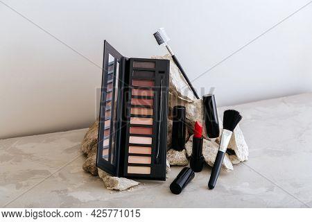 Makeup Cosmetics On Stone Pedestal. Red Scarlet Lipstick Eyeshadow Makeup Brushes On Gray Concrete B